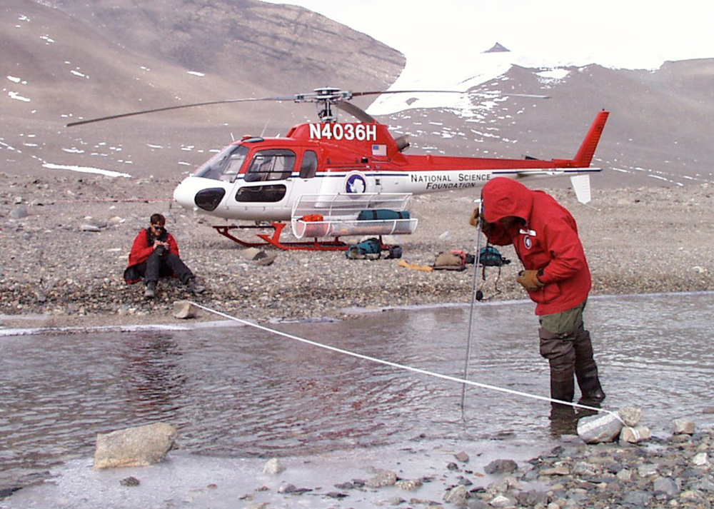Researchers measure water depth and velocity in the Onyx River, Antarctica. Photo:  Josh Landis, NSF, USAP.