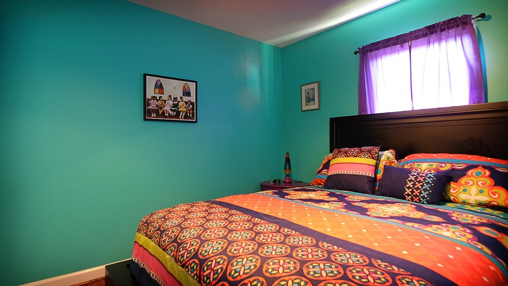 Teal walls against multicolored bed spread - Residential painting by Nash Painting Nashville TN
