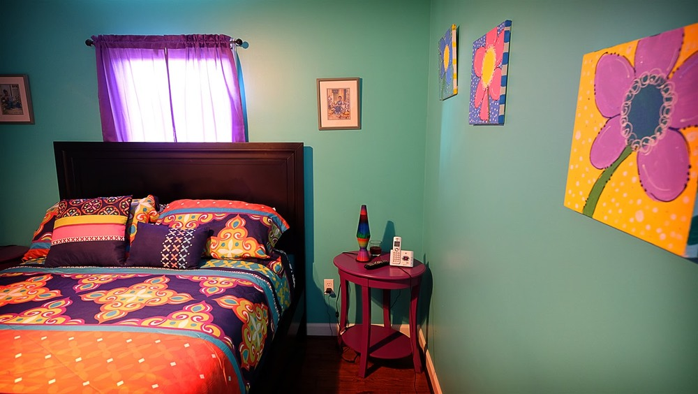 Teal walls against colorful bedding and flower canvas wall art - Residential painting by Nash Painting Nashville TN