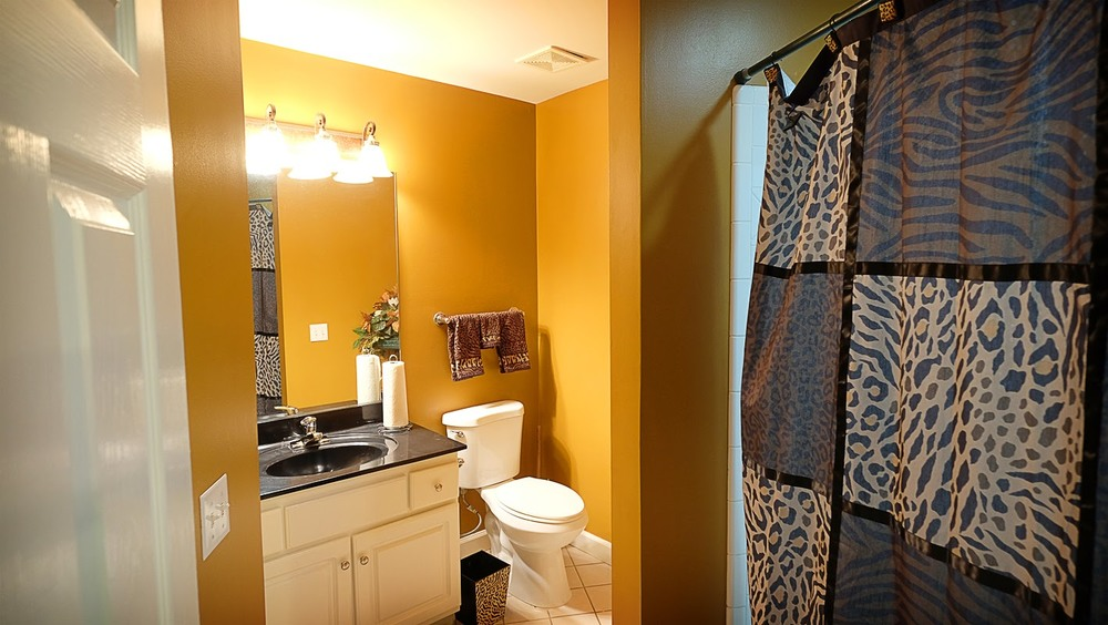 Gold / yellow walls, black and white bathroom vanity and animal print accessories - Residential painting by Nash Painting Nashville TN