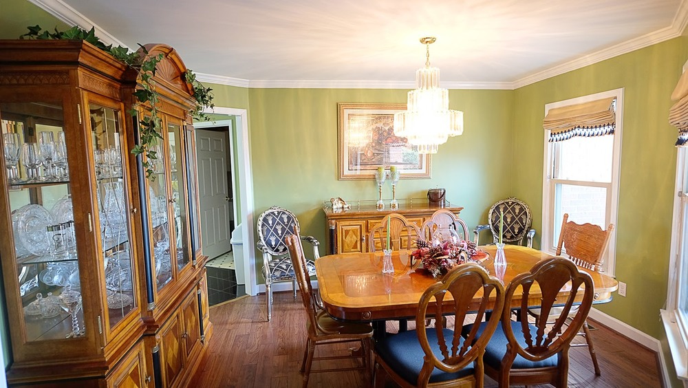 Light green walls with white crown molding, hardwood floors and oak dining room set - Residential painting by Nash Painting Nashville TN