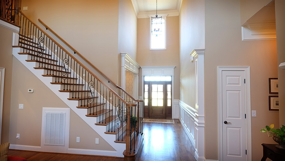 Light gray, white trim, vaulted ceilings, staircase, view of front door - Residential painting by Nash Painting Nashville TN
