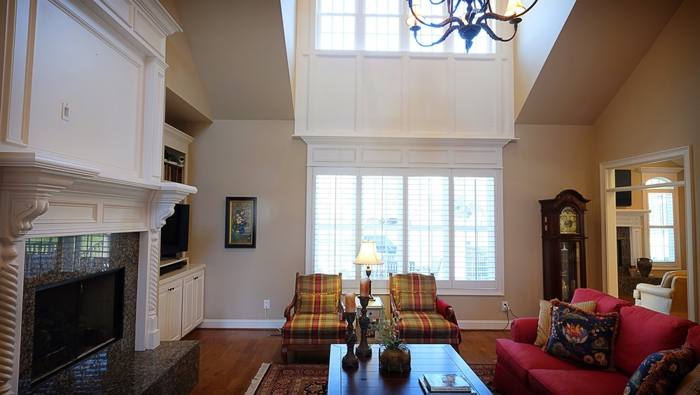 Large living area with vaulted ceilings, white trim, hardwood floors, tall windows - Residential painting by Nash Painting Nashville TN