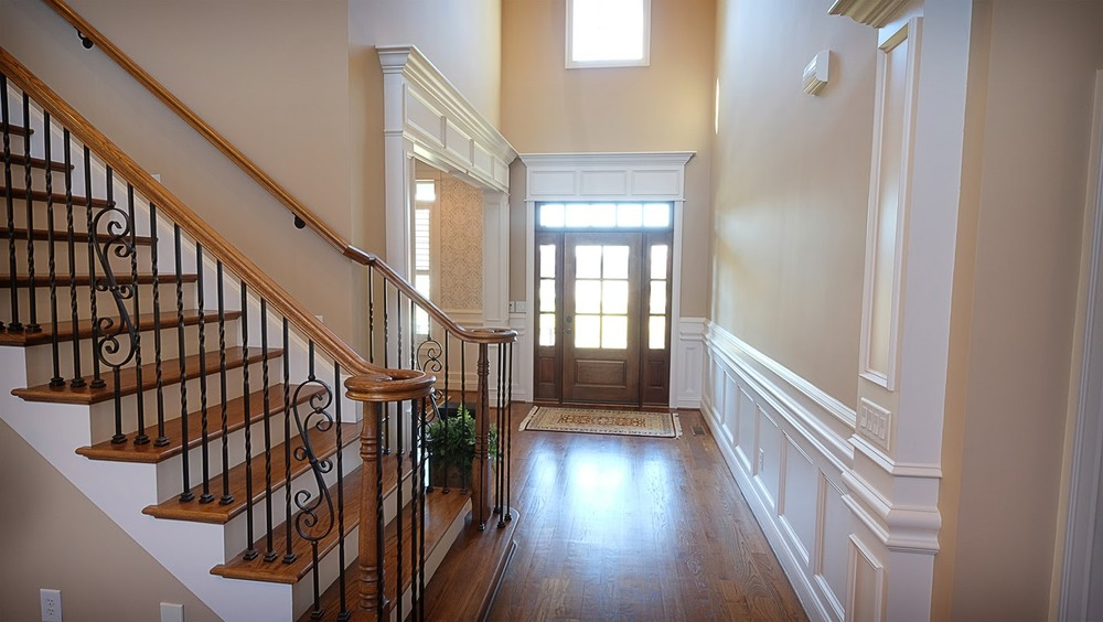 Entry way with vaulted ceilings, white decorative wood trim, staircase and hardwood floors - Residential painting by Nash Painting Nashville TN