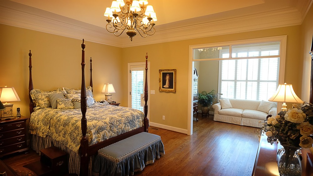 Light tan, taupe bedroom with sitting area, crown molding, white trim, hardwood floors - Residential painting by Nash Painting Nashville TN