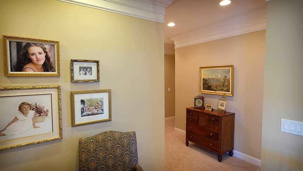 Light tan, taupe, living area with hallway, white trim, crown molding, carpeted floors - Residential painting by Nash Painting Nashville TN