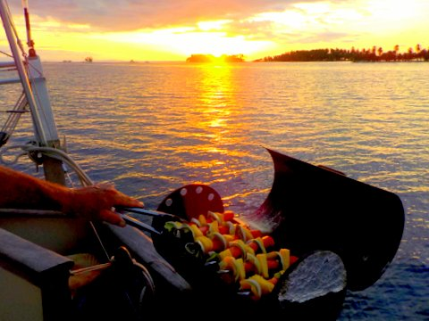 Grilling chirizoe kabobs with fresh pineapple at sunset