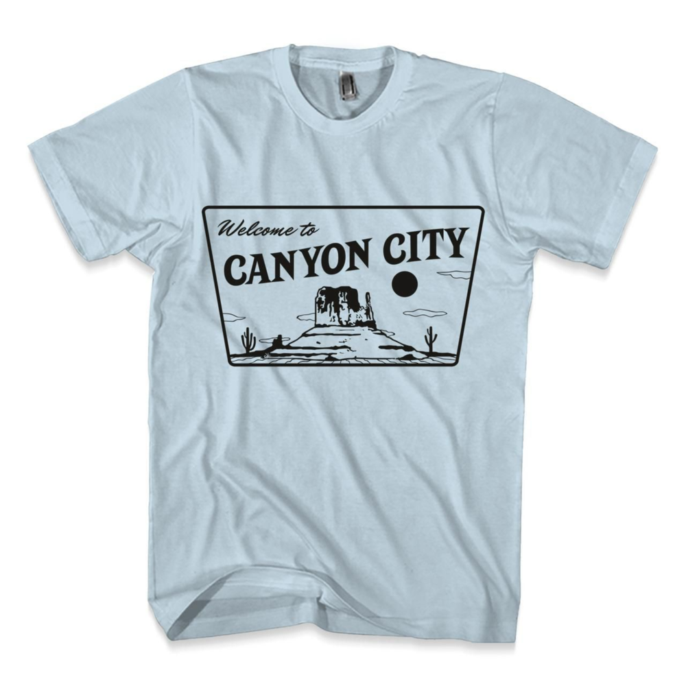Welcome to Canyon City   This t-shirt is perfect for the summer sun. Welcome to Canyon City printed on a light blue t-shirt. 100% cotton ensures a comfortable material with medium weight. This fashion fit comes in sizes Small to 3XL, so add a pop of color in your summer tee collection with this special Canyon City Tee!
