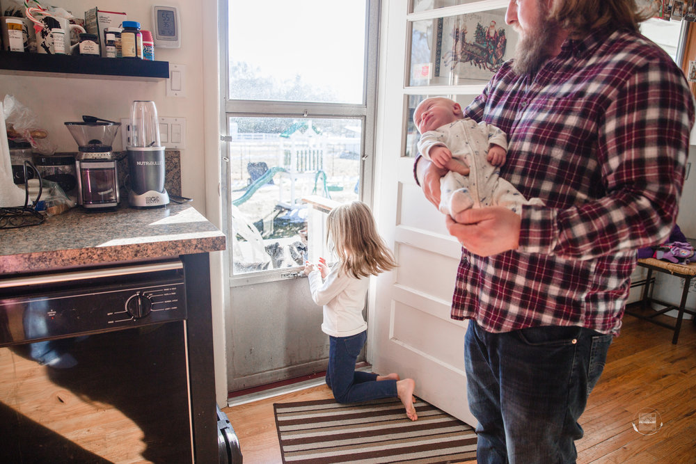 This is real life. In the kitchen as mom makes the bottle, big sister playing with the dog, and Dad holding baby.