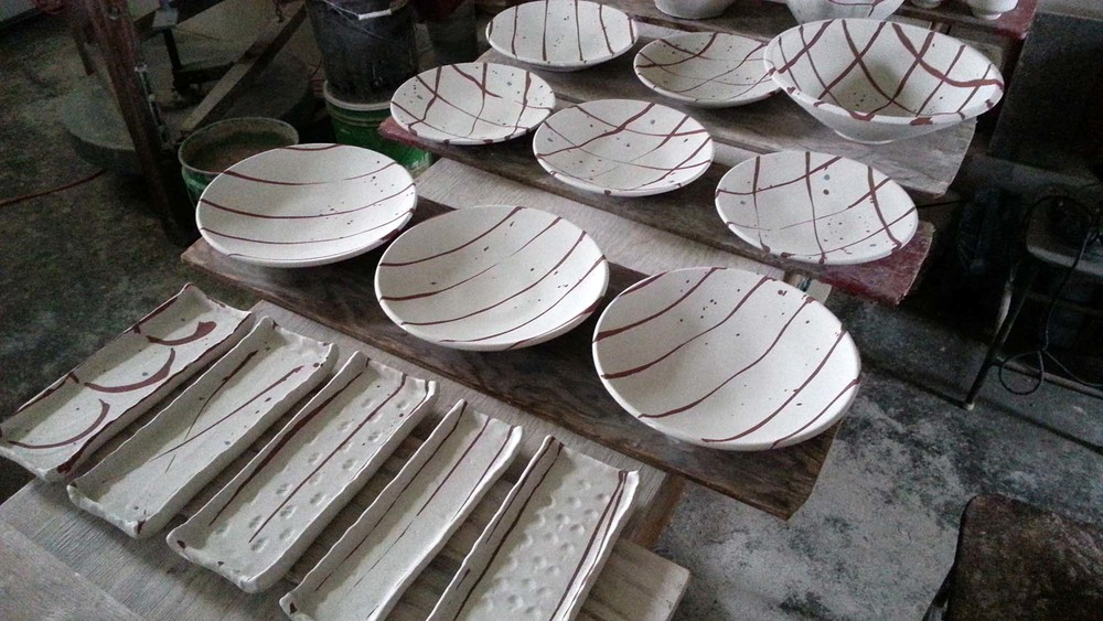 Plates and trays with raw glaze and iron oxide brush marks. Ready to be fired.