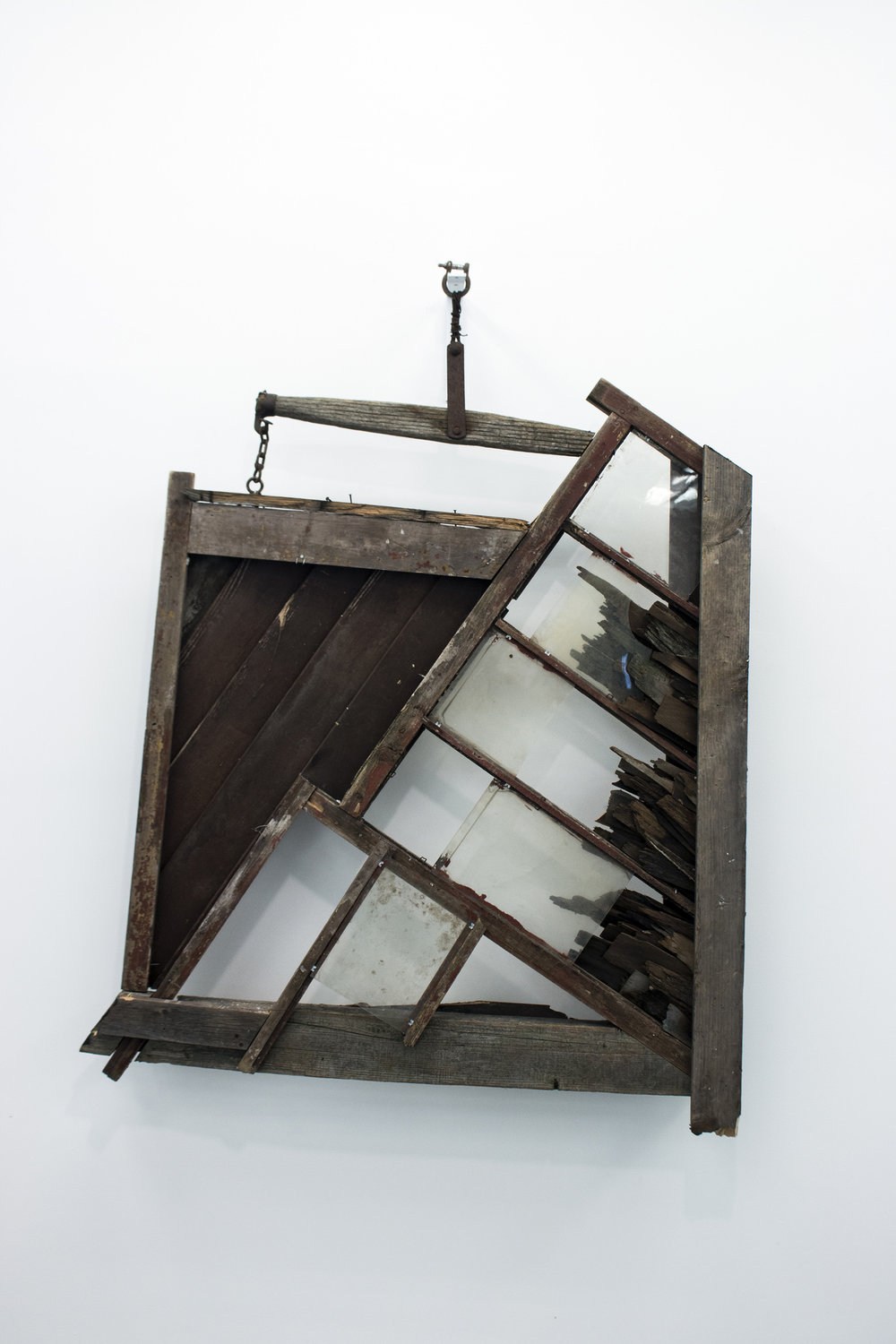 """Mended Pieces,"" Benjamin Quesnel's tobacco farm barn refuse assemblage, substantial and solid, yet precariously hung, at first seems wistful for a past Americana, but then turns cynical as we gaze through a window looking onto an opaque white wall."