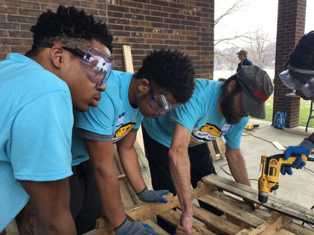 Jay (left), Divad and Ruth (far right) work with Build Corps mentor Bryan Huber on their bench.