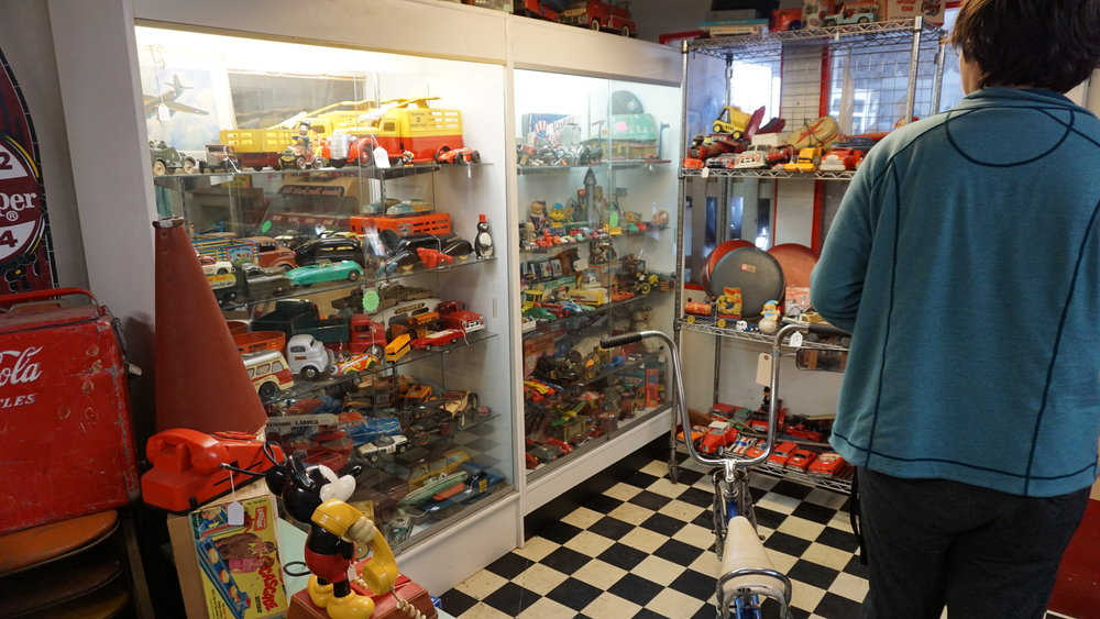 Customer Manny Vargas looks over the shelves of 50s era toy cars. Photo by Daniel Steele.