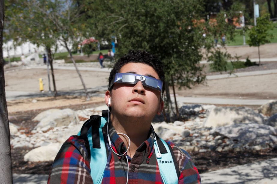 Miguel Verdin, business administration major, observes a partial eclipse at the Chaffey Quad on Aug. 22