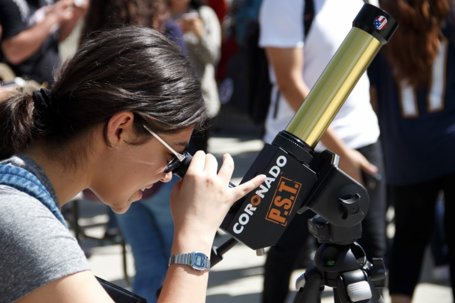 Daniella Brilnes, child development major, observes the partial solar eclipse through a telescope in the Rancho Quad on Aug. 22. Photo by Jullian Aiden Bravo