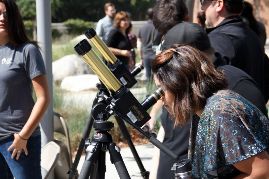 Yubel Svenson, educational program assistant for visual and performing art, looks through the lens of Coronado telescope in the Rancho Quad on Aug. 22. Photo by Jullian Aiden Bravo