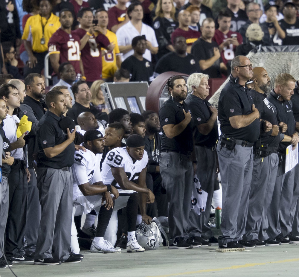 EJ Manuel and Amari Cooper of the Oakland Raiders kneel during the national anthem before facing off against the Washington Redskins on Sept. 24, 2017.
