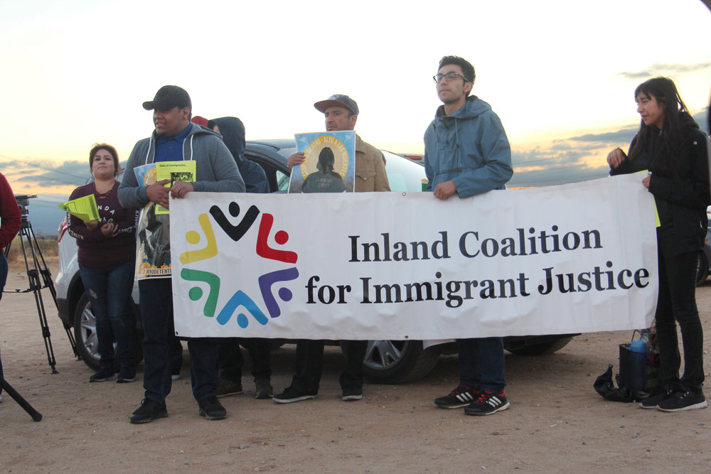Protesters holding a sign for the Inland Coalition for Immigrant Justice.