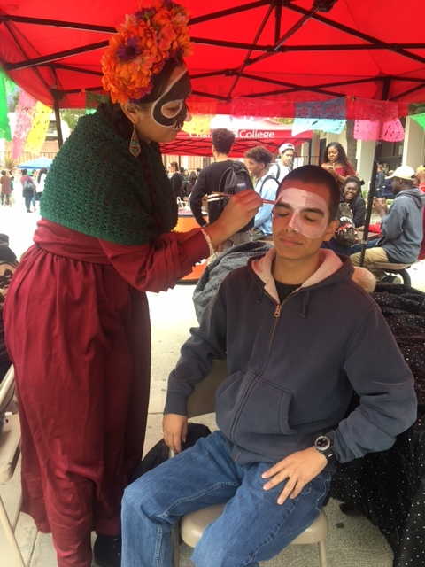 Artist Stephanie Serrano paints a calavera (skull) on dental assistant major, Eduardo Becerril's face during the Día De Los Muertos event on Chaffey's Rancho Cucamonga campus. The calavera face painting is a traditional aspect of the Día De Los Muertos event in Mexico.