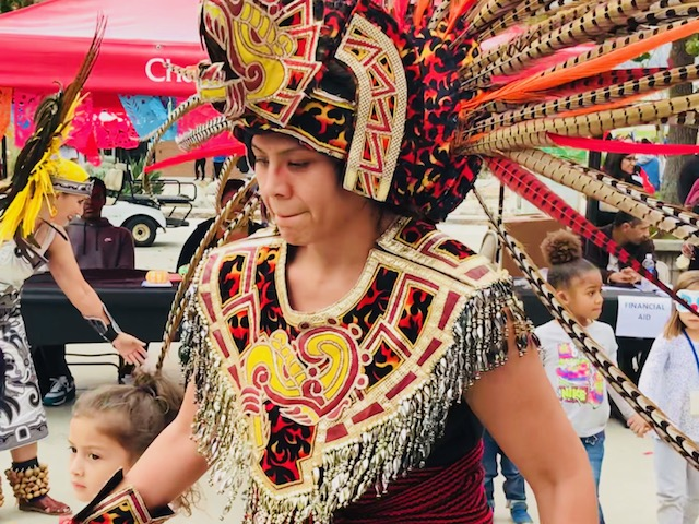 Danzantes del sol dancer invites along children to dance for Chaffey College's Dia de Los muertos celebration