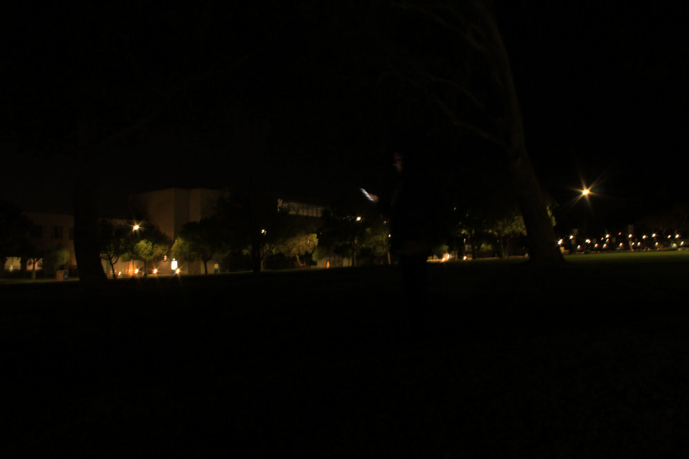 A student distracts herself with her phone as she walks through the darkness of Cal State San Bernardino.