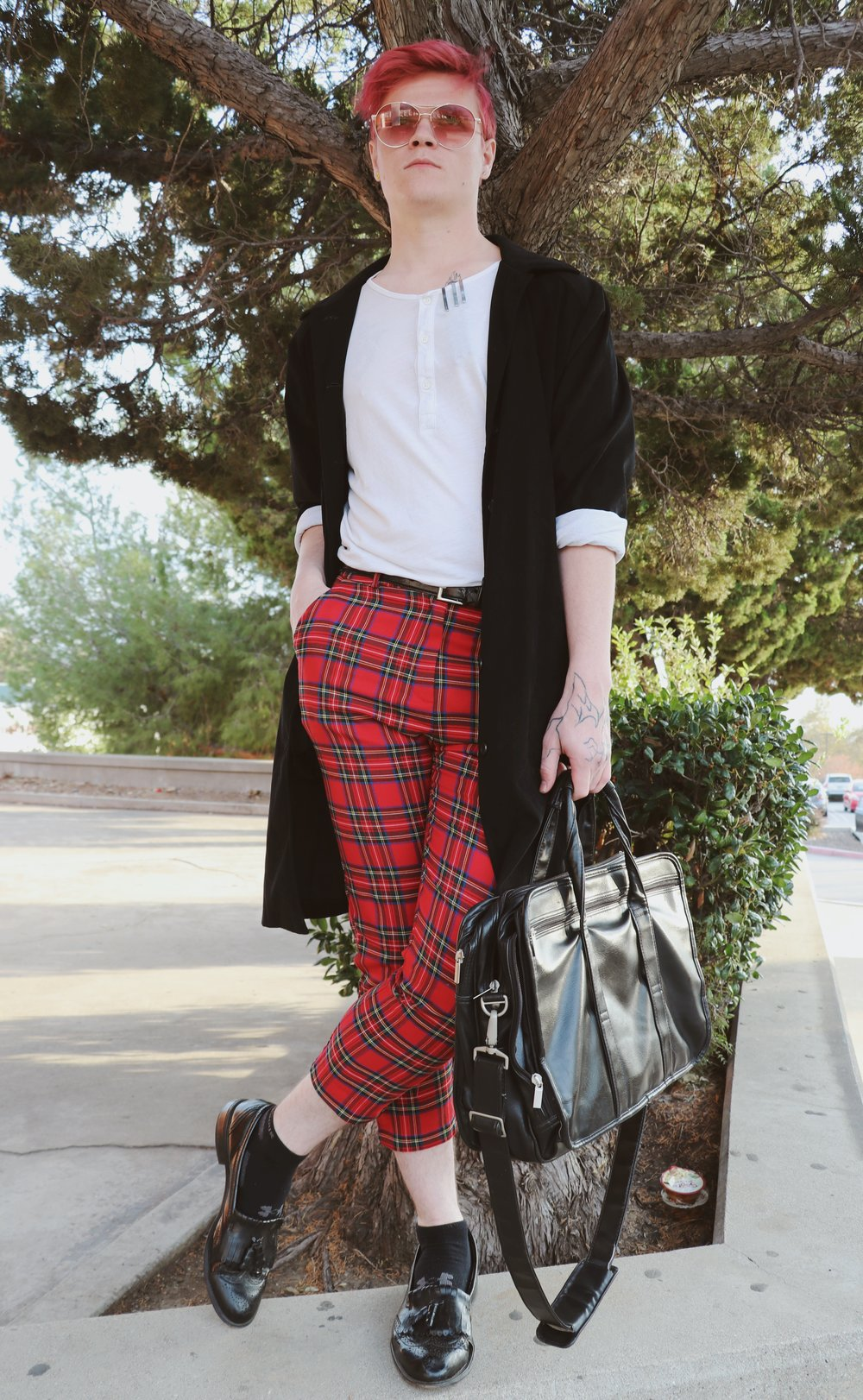Chaffey student Zachariah Jolin wears a modern, edgy street-style outfit with black and white top layers to compliment his plaid pants; accessorized from head to toe with shades, a black leather belt, bag and oxfords.