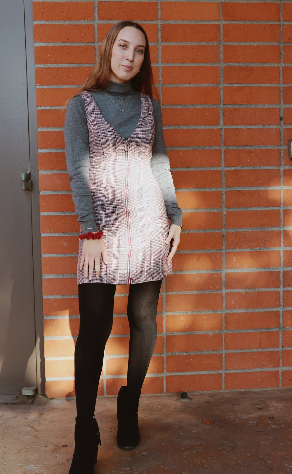 Chaffey student Raylene Camerano dresses in modern chic layers in a plaid dress with a turtleneck and black tights, finishing the look with black booties.
