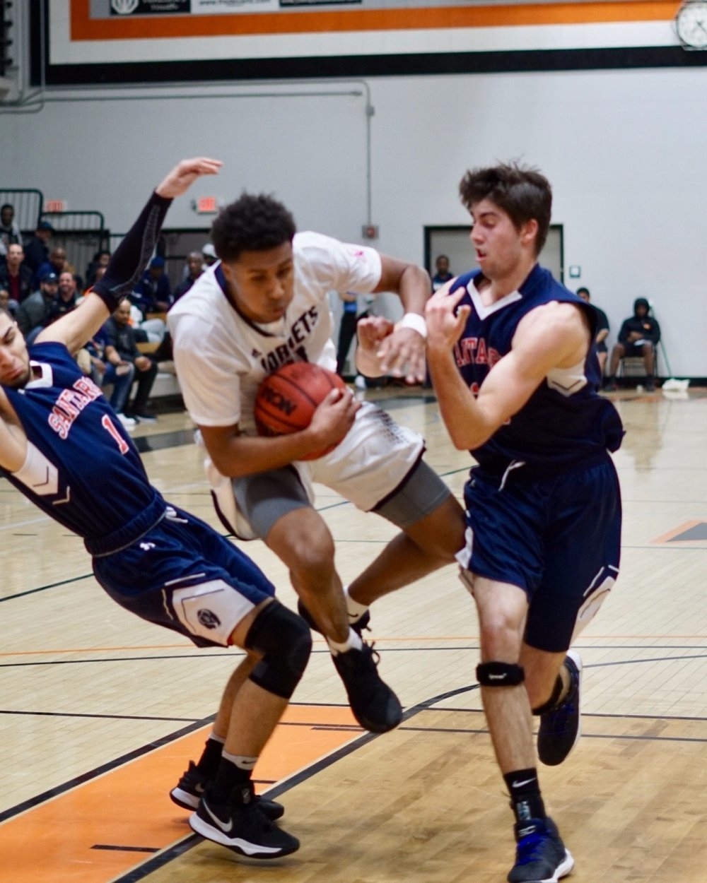 Fullerton College guard, Roger McCobb making his way to the rim defended by Santa Rosa's Skylar Chavez (33) and Atmar Mundu (1). Photos by Emmanuel Vargas.