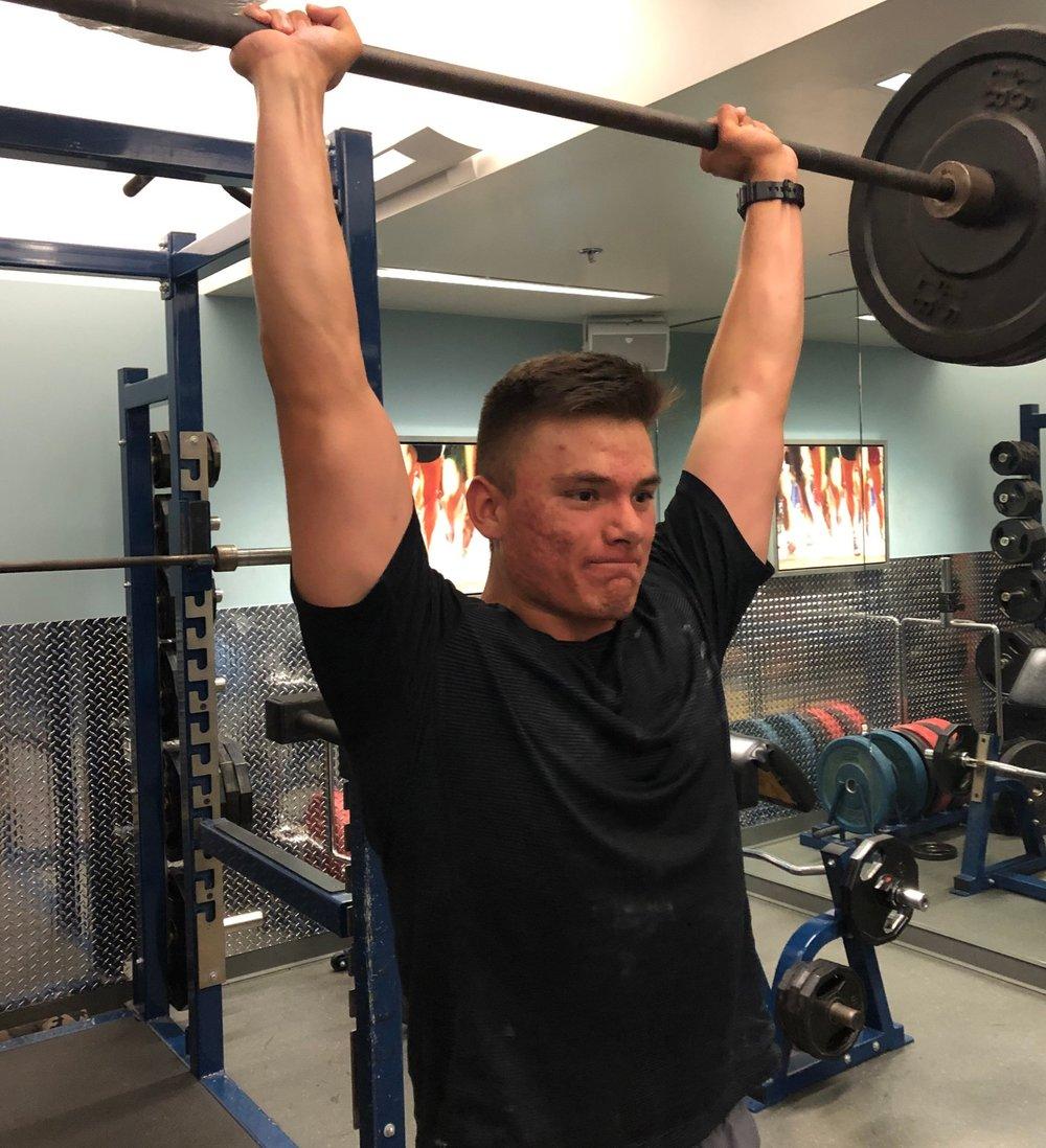 Beltran doing a heavy shoulder press. Photo by Edward Lopez.