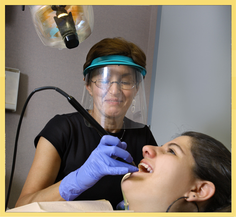Ema, our dental hygienist, cleans a patient's teeth. General dentistry is an important part of our practice.