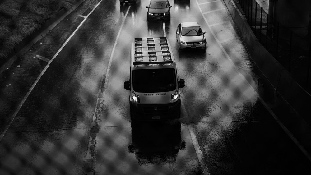 Cars pass under a Brooklyn overpass in the rain.