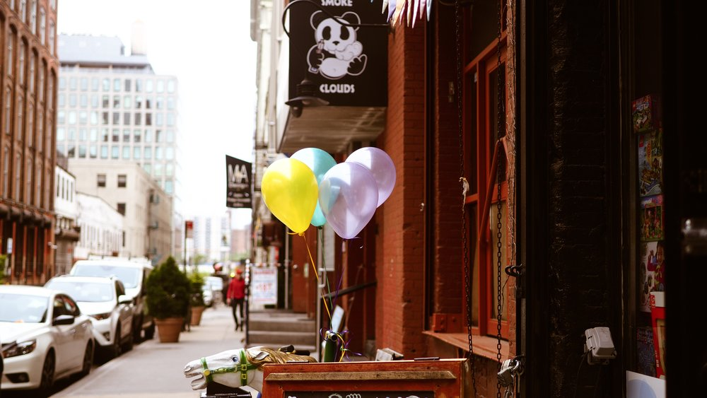 Balloons are tied to a sign on the street in Dumbo, Brooklyn, New York City.