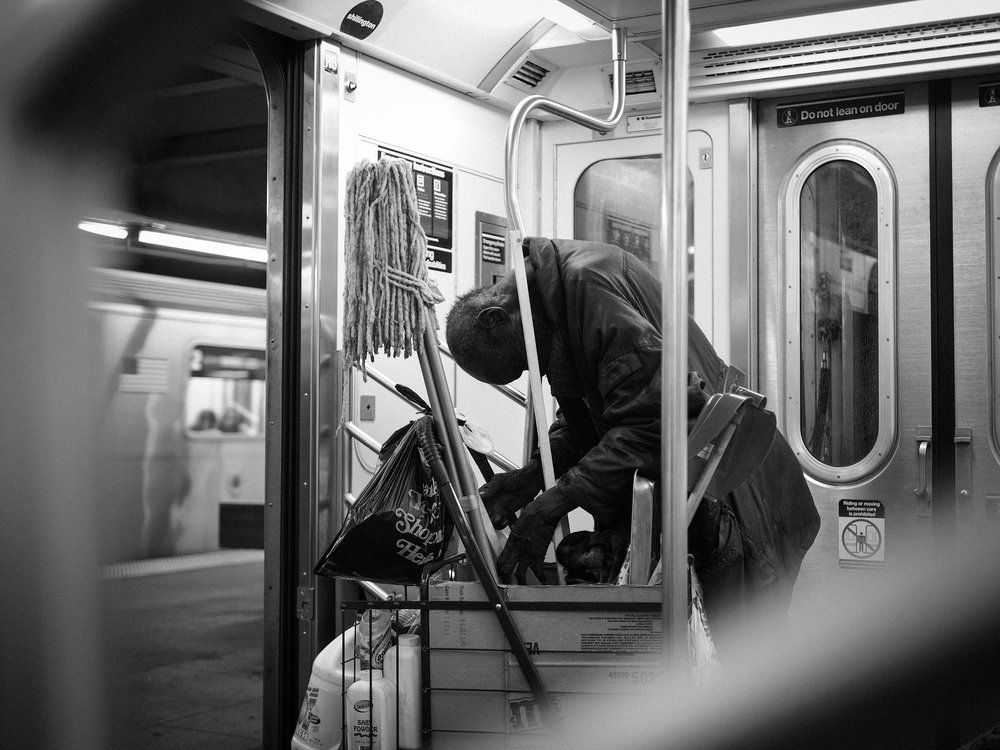 A homeless man searches through is belongings on a subway in New York City.