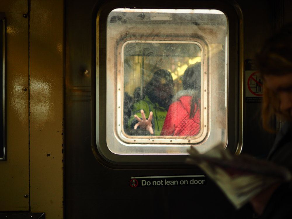 A man reaches out to a window on a train in New York City.