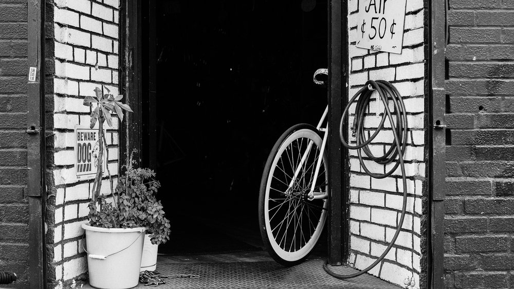 A bike sits outside a bicycle shop just off the street in Ridgewood, Queens, New York City.