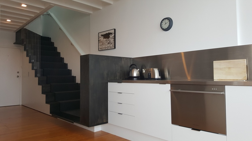 AFTER  A floating black plywood stair was installed in the entry, cleverly hiding the laundry and storage underneath.  The stair flows seamlessly into the industrial sized stainless steel kitchen.
