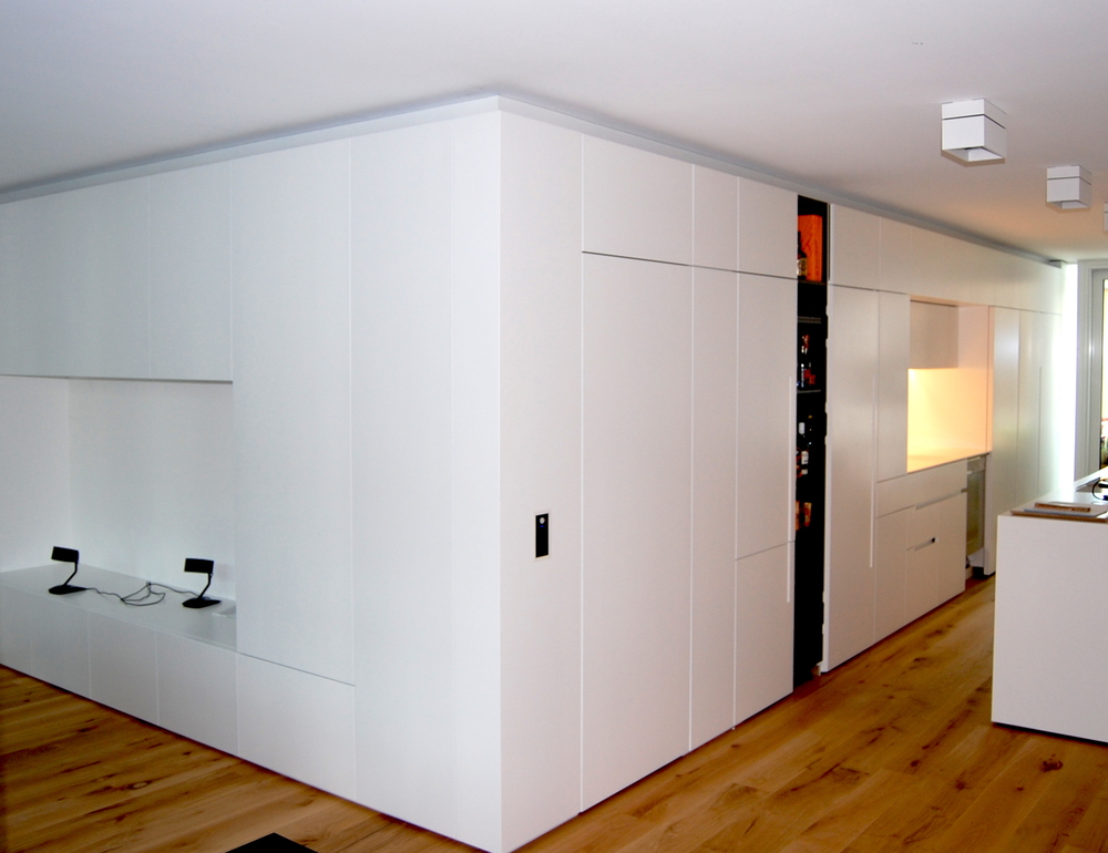 The carpentry works flow handsomely from one room to the next without cutting the space in this open concept apartment.