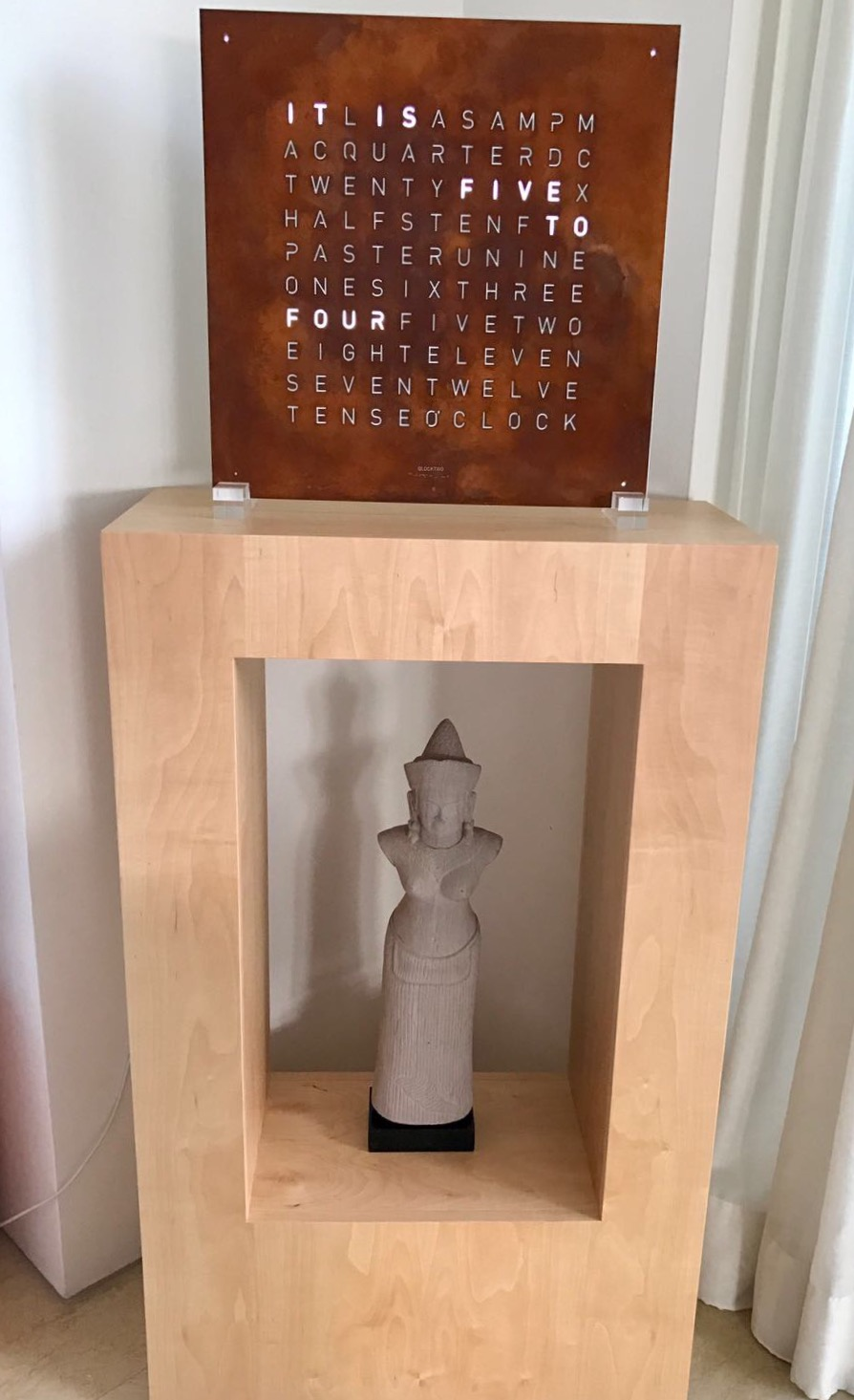 A solid Maple wood display stand to bring out the copper tone for the Swiss made word clock, that also houses a traditional Cambodian statue at the bottom.