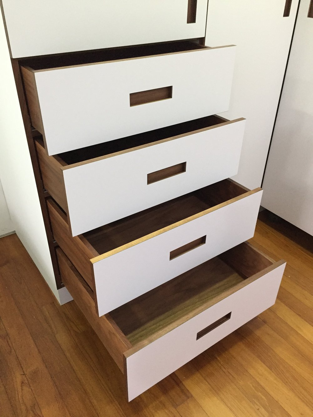 Exposed drawers with pocket handles in solid Walnut wood.