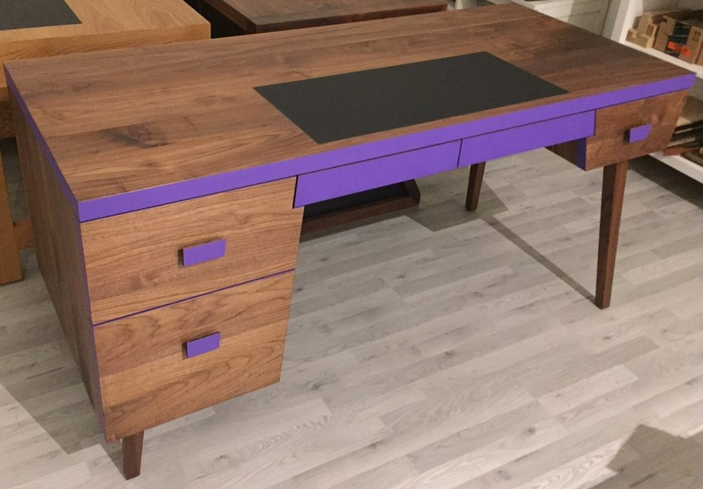 A young adult's study desk built in solid Walnut paired with trendy royal purple laminate and black leather insert for writing. Adding on a bit of tradition to this chic piece.
