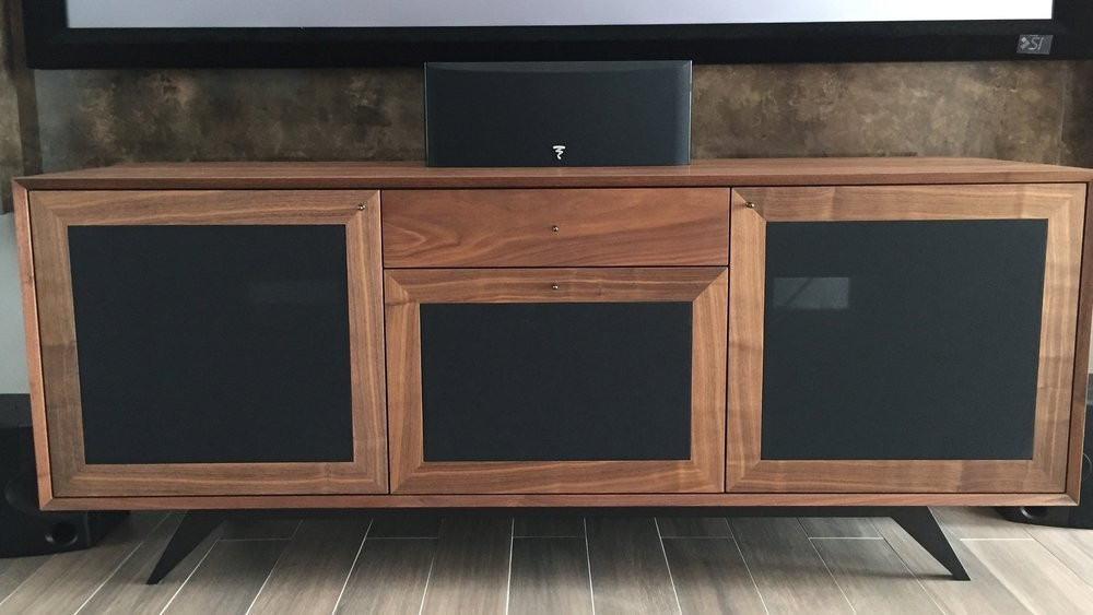 A sharp TV console built with Walnut veneer and black wire mesh for ventilation and remote controls to work without the need to open up the cabinet doors.