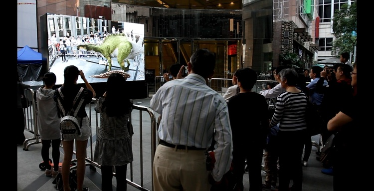 INDE's Appshaker BroadcastAR experience - visitors of the exhibit interacting with INDE's dinosaurs on a large screen
