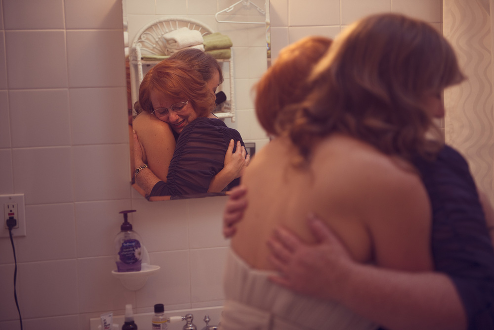 bride wedding dress mother daughter hug tears joy emotion