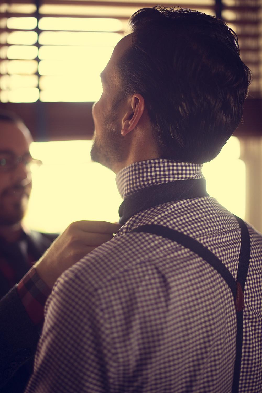 helping groom groomsmen suspenders tie