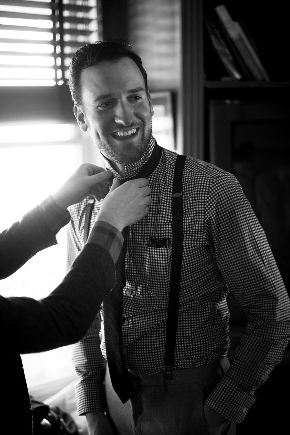 groom help tie preparing suit
