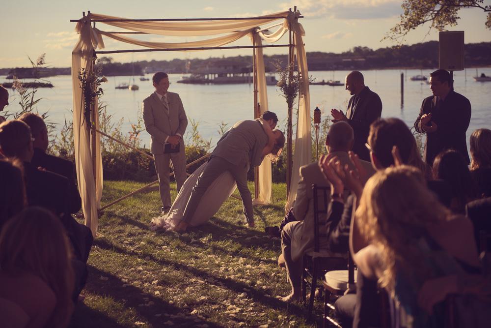 bride groom dip first kiss husband wife celebration wedding arch coast ocean New England