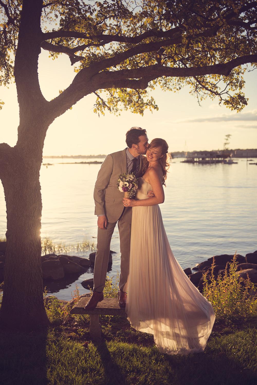 bride groom kiss sunset portrait bench tree beautiful husband wife coast ocean New England smooch romance