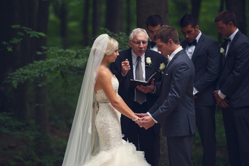 bride prayer holding hands groom ceremony outdoor rustic