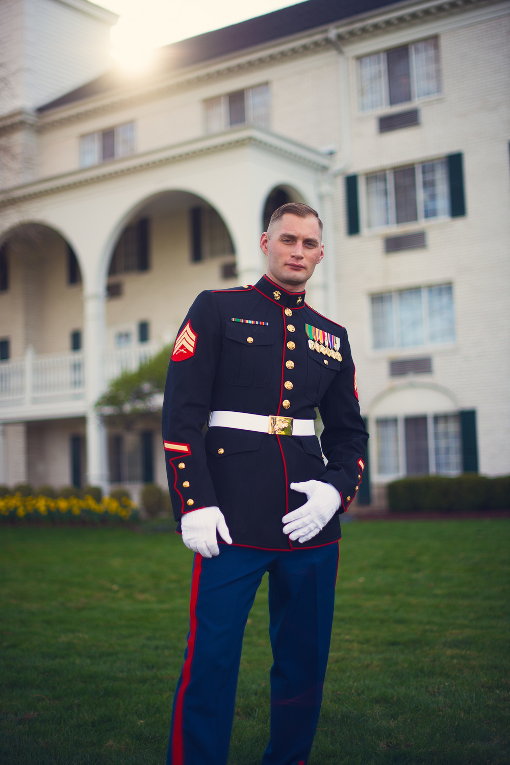 MIlitary garbed Groom stands in fron of hotel with sun flare THPHOTO