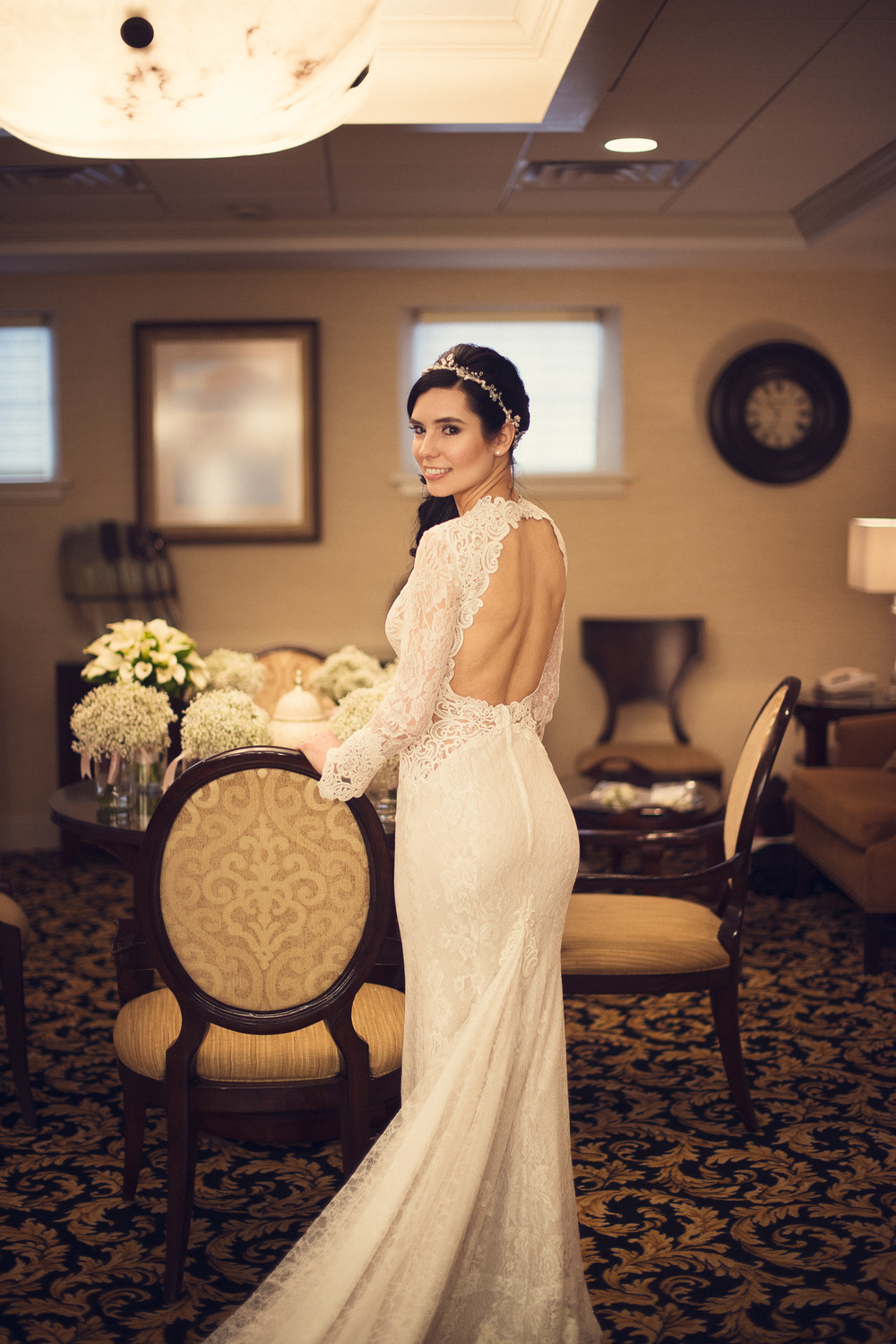 Bride with open back dress with hand on chair THPHOTO
